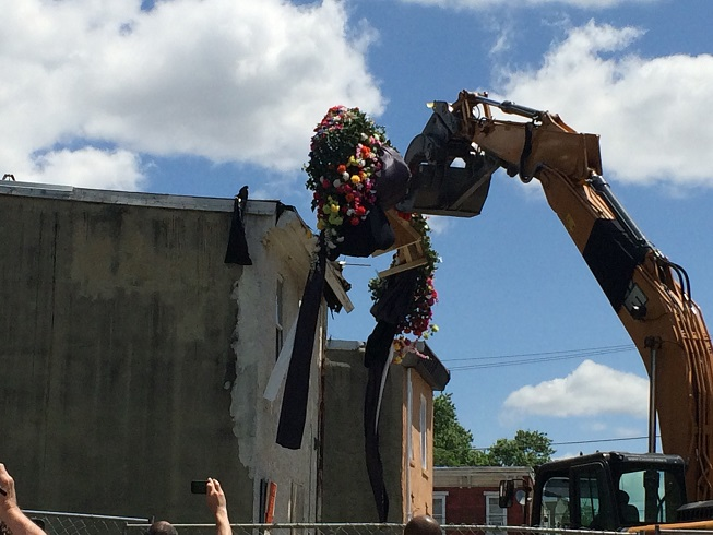 An excavator ceremoniously removes the crown of garlands.
